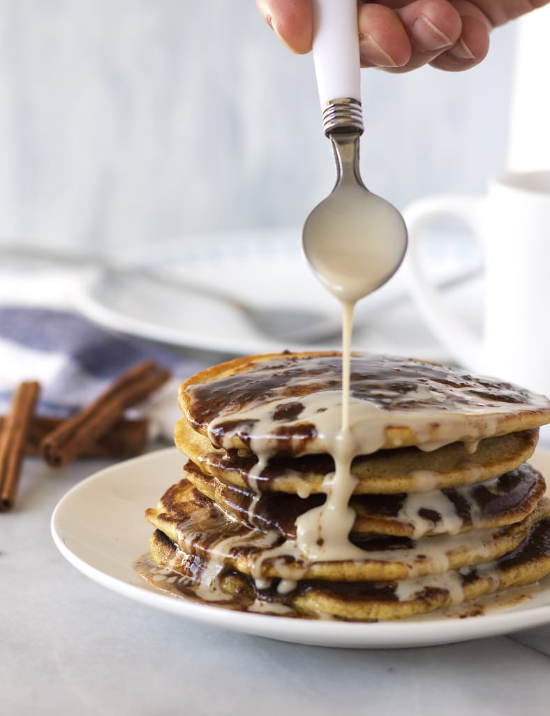 Cinnamon Bun Pancakes are the ultimate {secretly healthy} indulgent breakfast! The light and fluffy pancakes are smothered in sticky sweet cinnamon and sugar sauce then topped with a creamy icing syrup. They taste just like cinnamon buns, but they are easy, healthy, grain and gluten-free, and paleo! Packed with protein to provide energy, these decadent pancakes will be your new favorite weekend breakfast!
