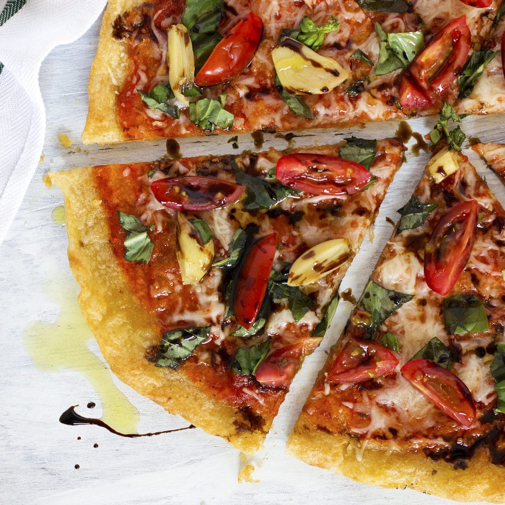 This garlicky Caprese Pizza is loaded with fresh Italian flavors that will keep you coming back for more! This sweet, savory, and salty flavor combo is surely to make your pizza night extra special. In addition, this healthy crispy thin crust is VEGGIE-based (and it's NOT cauliflower!!!)