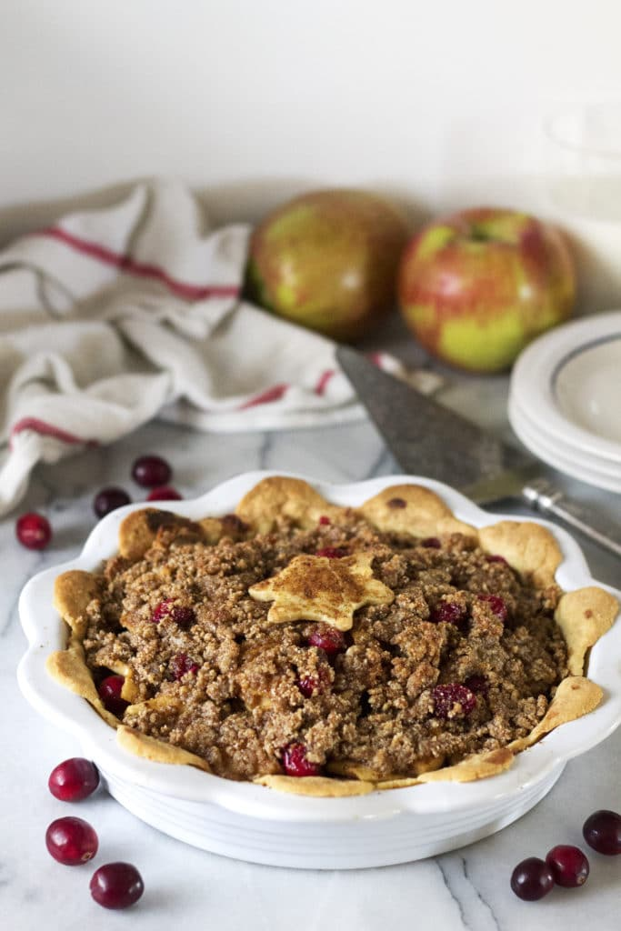 This Apple Cranberry Crumble Pie is full of sweet cinnamon decadence, topped with a buttery crisp crumb. The sweet apples and tart cranberries come together in perfect union to create the ultimate holiday pie. All your guests will adore this dessert and they will never ever guess it's gluten free, paleo, and healthy!